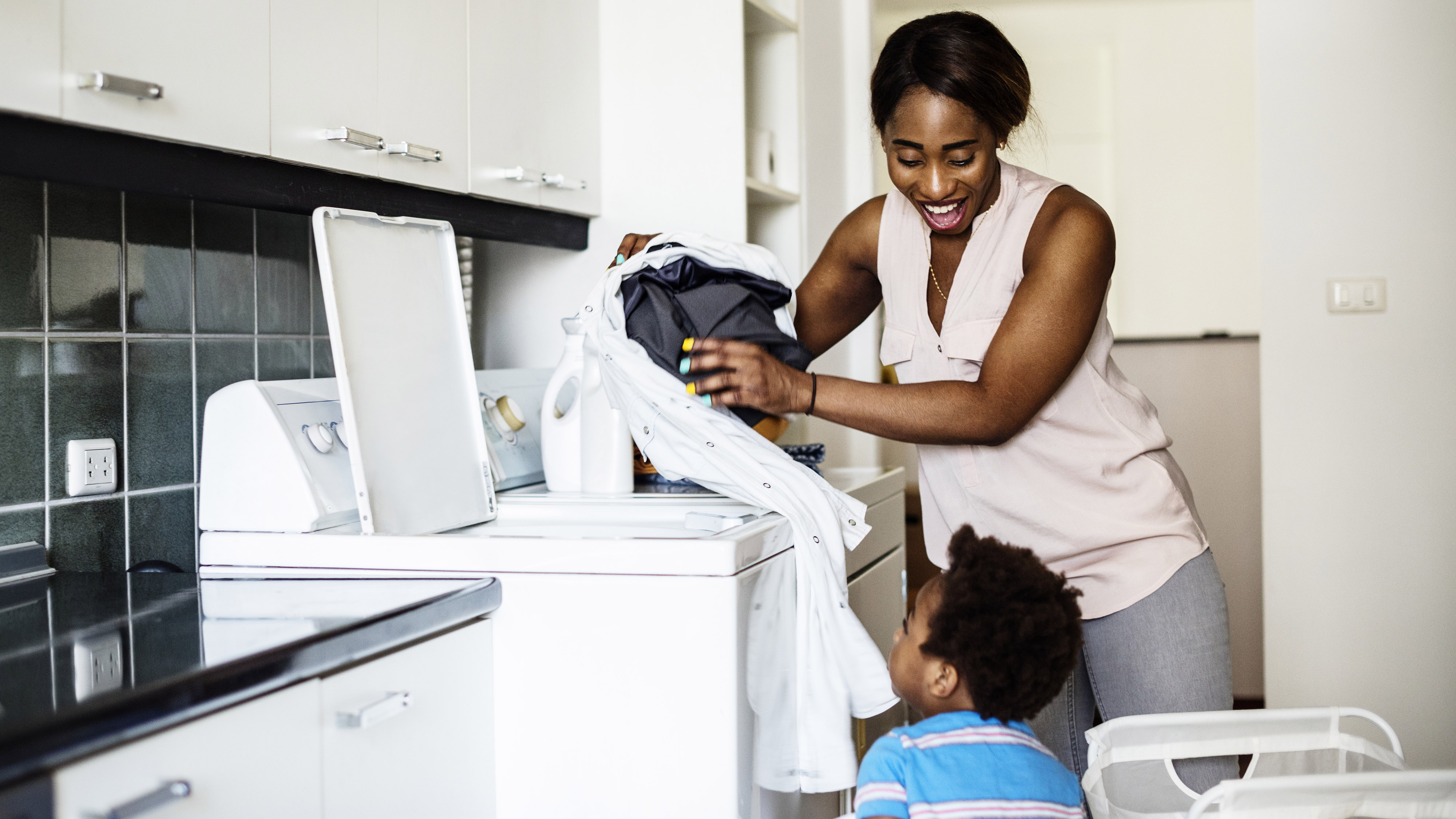 mother doing laundry with child watching