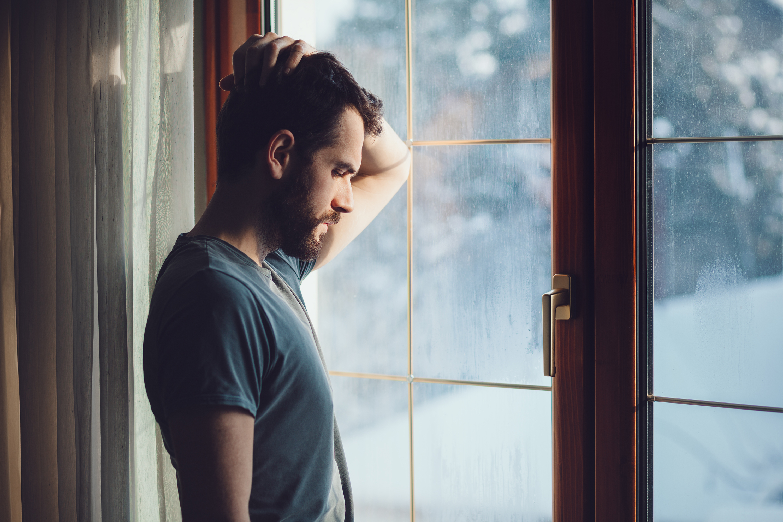 man looking sadly out of window